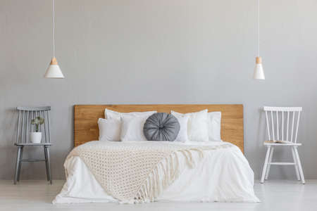 Blanket on wooden bed between chairs in grey bedroom interior with lamps and plant. Real photo