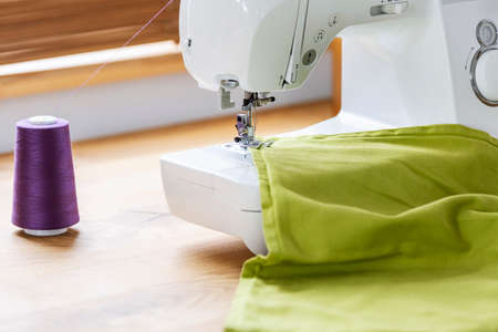 Close-up of a white sewing machine stitching a purple thread on a green fabric in a crafts room interior. Real photo.