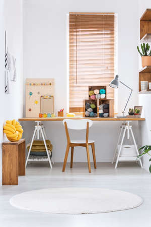 Wooden crates with dark and colorful yarn and other sewing tools on a wide workspace desk in a bright crafts room interior. Real photo.