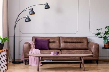 Purple pillow and pastel pink blanket placed on leather couch in real photo of bright sitting room interior with metal lamp, coffee table with tea cups and wainscoting on wall