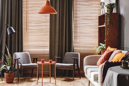 Grauer Sessel am orangefarbenen Tisch im dunklen Retro-Wohnzimmerinnenraum mit Vorhängen und Jalousien