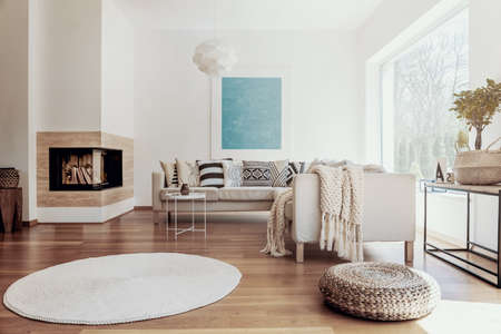 Large sky blue abstract art poster and a modern fireplace in a bright living room interior with dark hardwood floor Stock Photo - 107365891