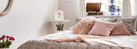 Panorama of pink pillows and blanket on bed in bedroom interior in english style with flowers. Real photo