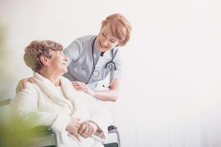 Positive doctor and smiling disabled elderly woman in the wheelchair. Copy space on white background