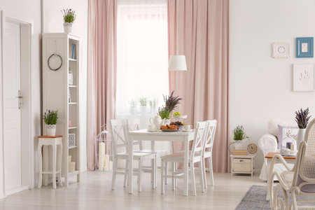 White flat interior with window with curtains, fresh lavender, dining table with breakfast and posters on wall in the real photo