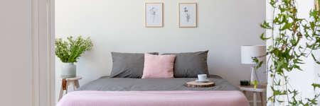 Graue und pastellrosa Bettwäsche auf Doppelbett mit Kaffeetasse in echtem Foto von hellem Schlafzimmerinterieur mit frischen Pflanzen und einfachen Postern