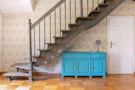 Een lichtblauwe driedeurskast die onder een grijze trap tegen een muur met bloemenbehang in een halbinnenland staat. Echte foto.