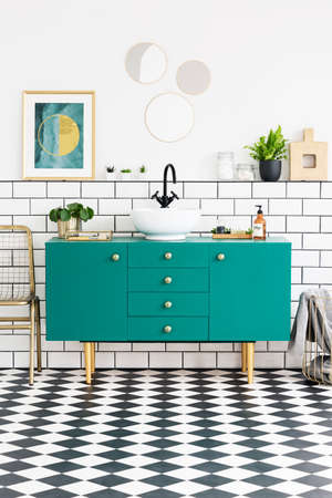 Mirrors and poster above green cabinet in bathroom interior with gold chair and plants. Real photo