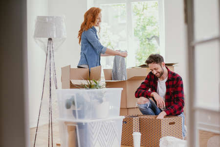 Young marriage packing stuff into boxes during relocation to new home