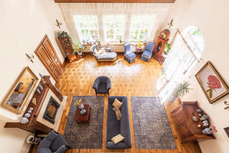 Top view of a luxurious high ceiling living room interior in a mansion. Cobalt blue armchairs and a couch in front of a fireplace, a cabinet, a settee and other furniture on a parquet. Real photo Stock Photo - 107677605