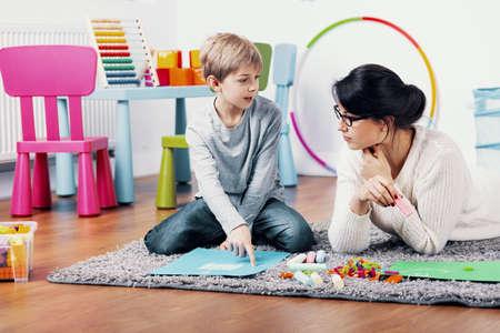 Pittura del bambino su carta durante le lezioni di arte con l'insegnante della scuola