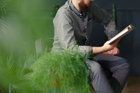Close-up of man relaxing while reading book next to plants Stock Photo