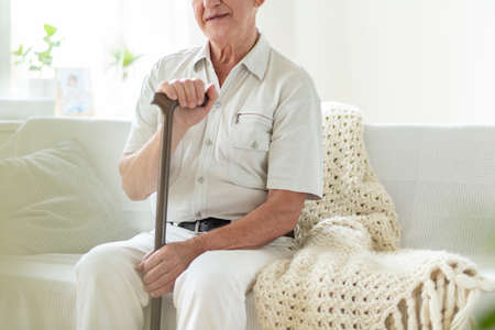 Close-up of elderly man with walking stick in a nursing house