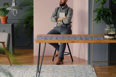 Hipster with beard holding a book while sitting at table in modern interior Stock Photo