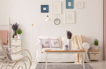Real photo of white living room interior with fresh lavender, posters on wall, coffee table with candles and couch with cushions Standard-Bild - 107678570