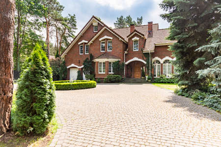 Large cobbled driveway in front of an impressive red brick English design mansion surrounded by old trees 스톡 콘텐츠