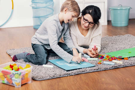 Mother and autistic boy drawing a picture on the floor at home