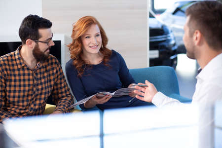 Couple looking at car offer and talking to a dealer in a car showroom Stockfoto