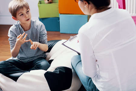 Child talking with teacher during extracurricular classes at home 写真素材