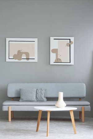 Wooden white table in front of grey sofa in minimal living room interior with paintings. Real photo Stock Photo