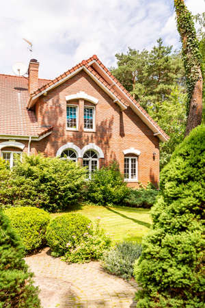 A garden with evergreens, trees, shrubs and grass in the backyard of a red brick luxurious English style house.