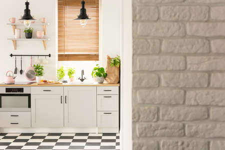 Grey brick wall in bright kitchen interior with lamps above countertop and checkered floor. Real photo
