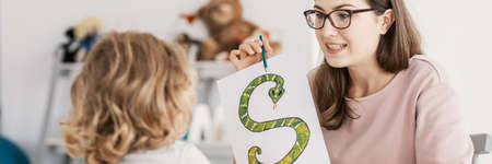 Panorama of woman teaching the child the alphabet with snake picture