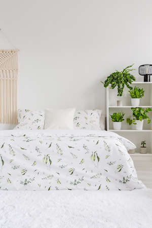 Scandinavian style bedroom interior with green plants pattern on white bedding lying on a bed. Fluffy rug on the floor. Empty wall in the background. Real photo.