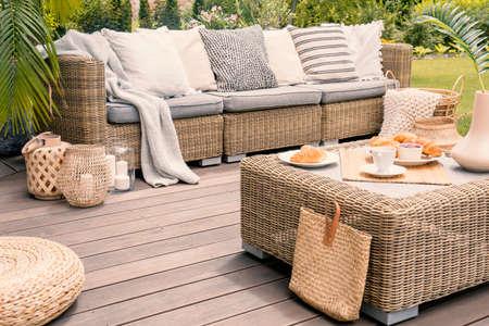 Patio de mimbre con cojines beige de pie sobre una plataforma de madera. Desayuno en una mesa en el porche de un patio trasero.