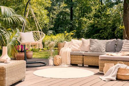 Een groot terras met een comfortabele vrijetijdsbank met kussens, een tafel en een touwschommel in een groene tuin tijdens een zonnige vakantie.
