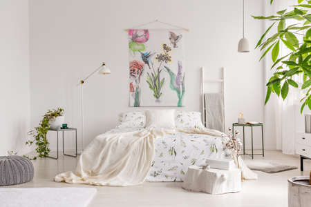 A bright eco friendly bedroom interior with a bed dresses in green plants pattern white linen. Fabric painted in flowers and birds on the background wall. Real photo.