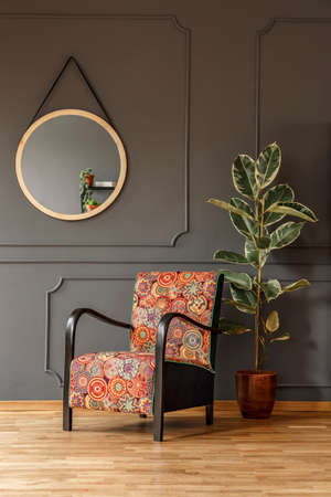 Ficus next to patterned armchair in grey living room interior with round mirror. Real photo