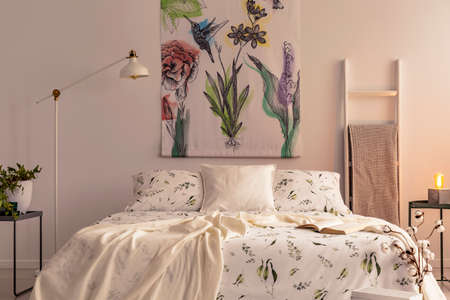 Flowers and a hummingbird painted on the fabric above a bed which is dressed in green plants pattern light color bedding in a cozy bedroom interior. Real photo.