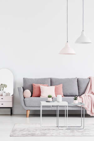 Lamps above table on carpet in white living room interior with pink pillows on grey sofa. Real photo