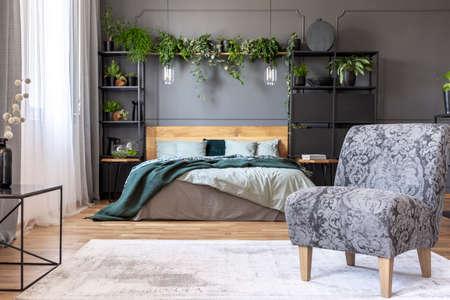 Fauteuil gris à motifs à l'intérieur de la chambre avec des plantes et des lampes au-dessus du lit en bois. Vrai photo Banque d'images