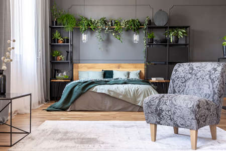 Patterned grey armchair in bedroom interior with plants and lamps above wooden bed. Real photo