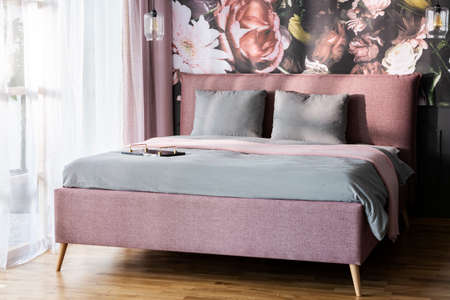 Grey cushions on pink bed in bright hotel bedroom interior with flowers wallpaper. Real photo
