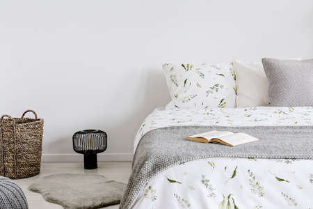 close-up of a bed with eco cotton and wool bedding and pillows in a bright bedroom interior. Real photo. Stock Photo