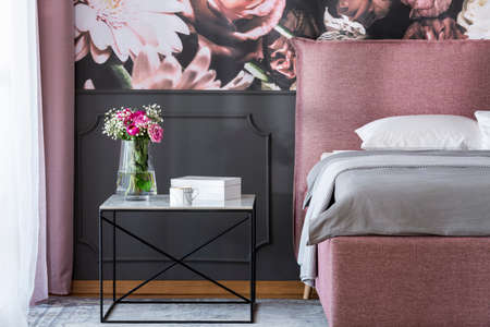 Flowers on black table next to pink and grey bed in bedroom interior with wallpaper. Real photo Stock fotó