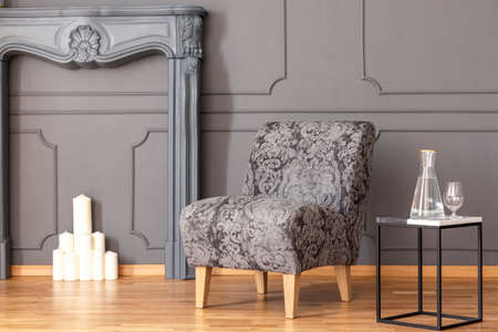 Table next to grey armchair in elegant living room interior with candles under faux fireplace. Real photo