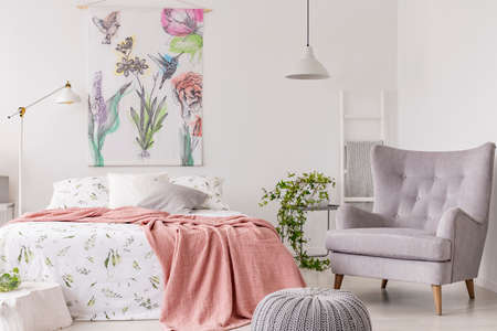A sunny bedroom interior with a bed dressed in green pattern white linen and a peach blanket. Gray comfortable armchair beside the bed and a textile print of flowers and birds above. Real photo. 스톡 콘텐츠