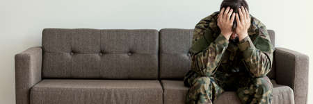 Soldier in uniform sitting on a sofa, waiting for his his appointment with a psychotherapist Stockfoto