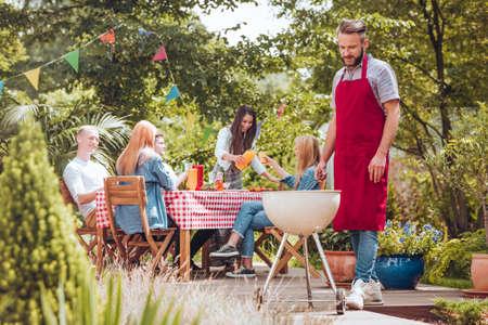 Ein junger Mann, der eine burgunderfarbene Schürze trägt, die auf einem weißen Grill kocht. Leute, die an einem Tisch sitzen und Spaß während einer Feier im Hinterhof haben.