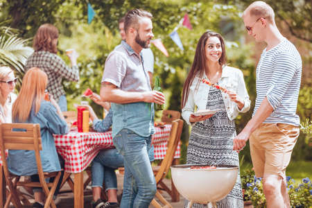 Two men flirting with a beautiful woman while standing next to a white grill with shashliks. Other people by a table in the background. Standard-Bild - 107792480
