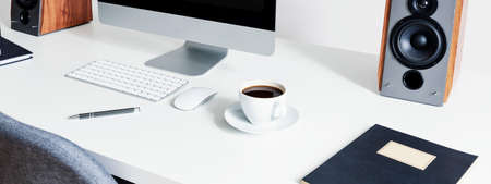 Close-up on a cup of coffee next to a computer mouse and keyboard on white desk in an interior for a freelancer. Real photo