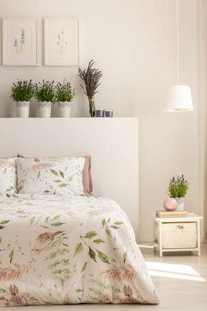 Lámpara sobre el mueble junto a la cama con plantas en el cabecero en el interior del dormitorio femenino. Foto real Foto de archivo