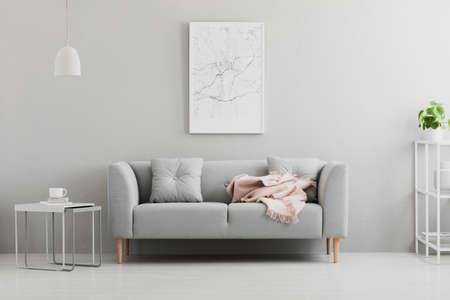 Plakat über grauem Sofa mit rosa Decke im Wohnzimmerinnenraum mit weißer Lampe und Pflanze. Echtes Foto