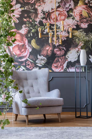 Gold chandelier above grey armchair in living room interior with flowers wallpaper. Real photo Stock fotó