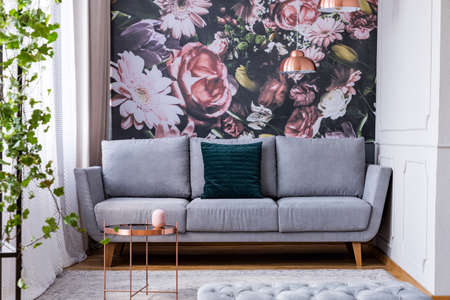 Copper table on carpet and green pillow on grey couch in flowers living room interior. Real photo Zdjęcie Seryjne - 107852911