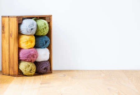 Close-up of a colorful yarn stack in a wooden crate by a white wall and copy space. Real photo. 版權商用圖片 - 107794642